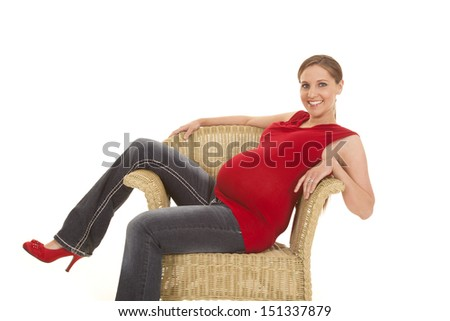 A pregnant woman sitting in a chair smiling. - stock photo