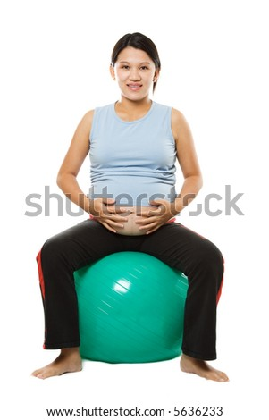 A pregnant woman sitting on an exercise ball