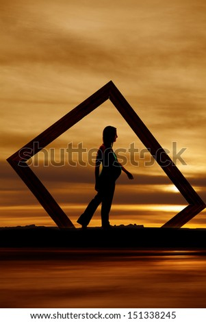 A pregnant woman walking framed in a picture frame. - stock photo