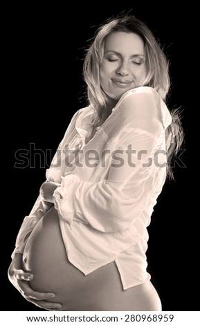 A pregnant woman with drawn belly in anticipation of the child. family values - stock photo