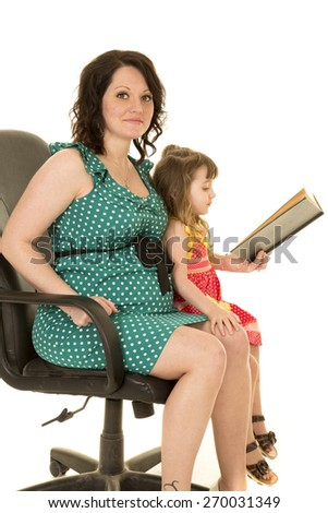 a pregnant woman with her daughter on her lap reading a story. - stock photo