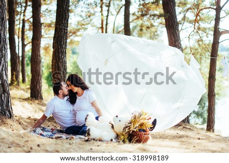 A pregnant woman with her husband at a picnic. Happy pregnant couple family