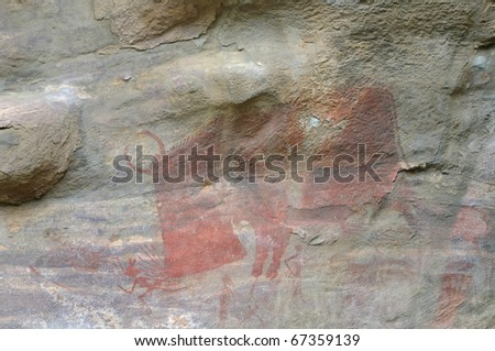 A prehistoric cave painting in Bhimbetka -India , a world heritage site which shows a bison pursuing hunter. - stock photo