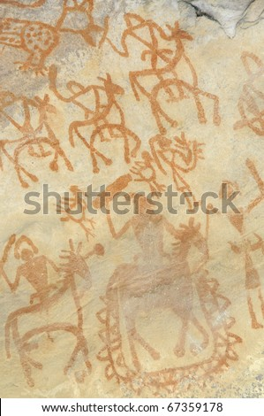 A prehistoric cave painting in Bhimbetka -India , a world heritage site which shows  a king on his horse followed by his soldiers. - stock photo