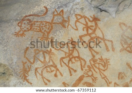 A prehistoric cave painting in Bhimbetka -India , a world heritage site which shows animals and men. - stock photo