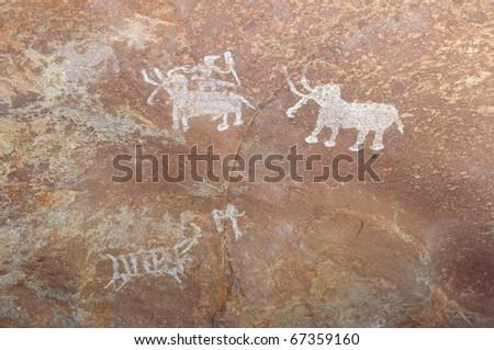 A prehistoric cave painting in Bhimbetka -India , a world heritage site which shows  men   and  animals. - stock photo