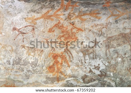A prehistoric cave painting in Bhimbetka -India , a world heritage site which shows men hunting and gathering. - stock photo