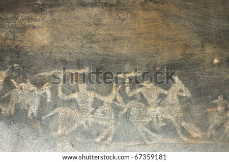 A prehistoric cave painting in Bhimbetka -India , a world heritage site which shows  men on their horses going out for hunting. - stock photo