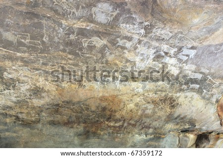 A prehistoric cave painting in Bhimbetka -India , a world heritage site which shows  series of paintings of different animals. - stock photo