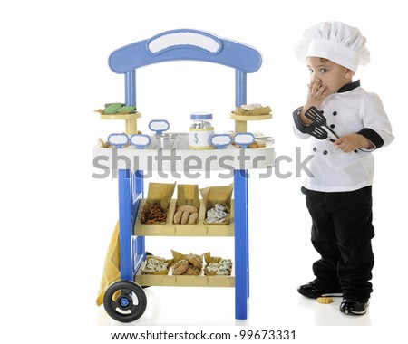 "A preschool ""baker-chef"" snitching cookies from his vending stand.  Signs on the stand are left blank for your text.  On a white background. - stock photo"