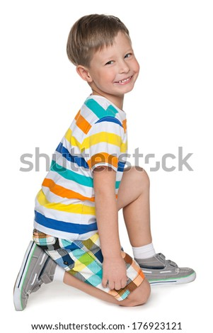 A preschool blond boy is sitting on the white background - stock photo