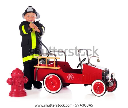 A preschool boy by a fire truck and hydrant and wearing fireman gear, points his hose at the viewer.  Isolated on white. - stock photo