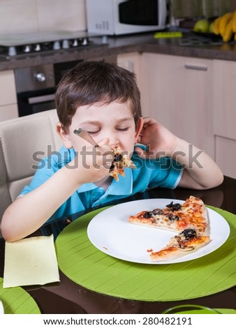 A preschool boy eat pizza in the kitchen - stock photo