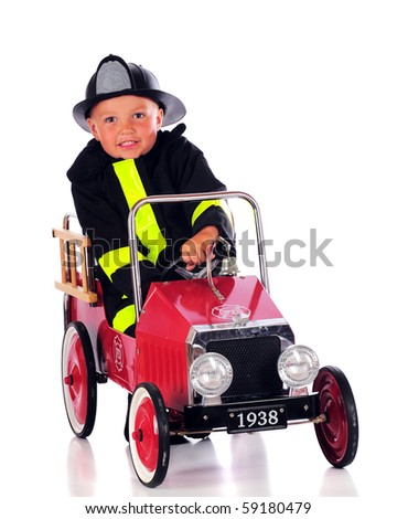 A preschool boy in fireman's gear, driving an old-fashioned ride-in fire truck.  Isolated on white. - stock photo