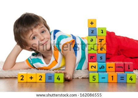 A preschool boy is playing with blocks on the floor - stock photo