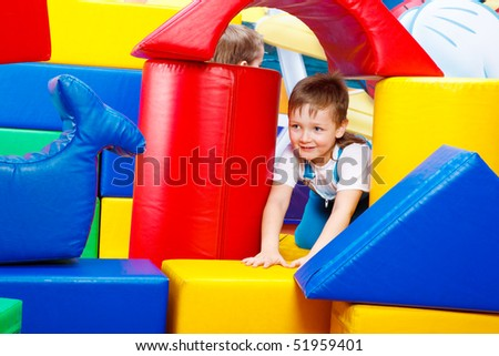 A preschool boy playing in the large bricks tower - stock photo