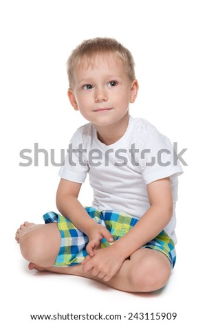 A preschool boy sits on the floor against the white background - stock photo