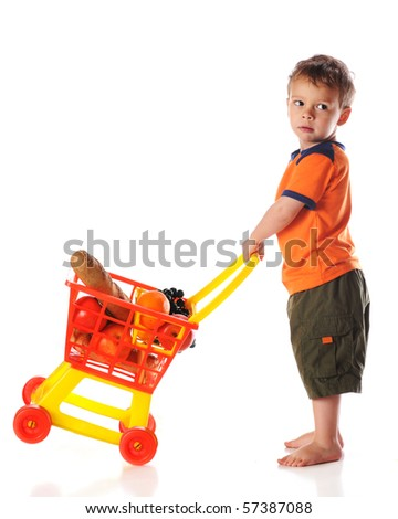 A preschool boy tipping a toy cart full of groceries.  Isolated on white. - stock photo