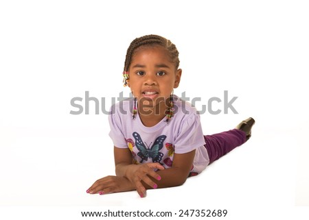 A preschool child laying on the floor isolated on white