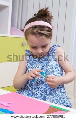 A preschool girl use glue for homework received from kindergarten - stock photo