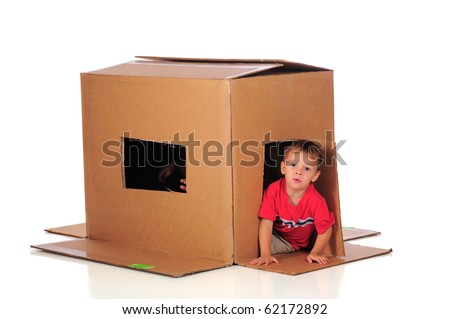 A preschooler coming through the door of his cardboard box, while his brother waves fingers through the window.  Isolated on white. - stock photo