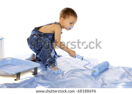 A preschooler painting a floor with a roller from a paint pan.  Isolated on white. - stock photo