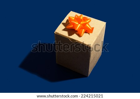 A present in a corrugated cardboard box with an orange ribbon - stock photo