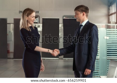 A presentable male manager in a suit shakes hands with a beautiful girl in a big bright office. Both are smiling.