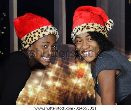 A preteen and teenage sister delightedly smiling at the viewer wearing Santa hats by a Christmas light decorated window.