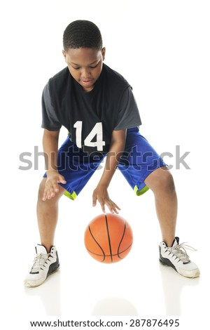 A preteen athlete rapidly dribbling his basketball close to the floor.  Motion blur on hands and ball.  On a white background. - stock photo