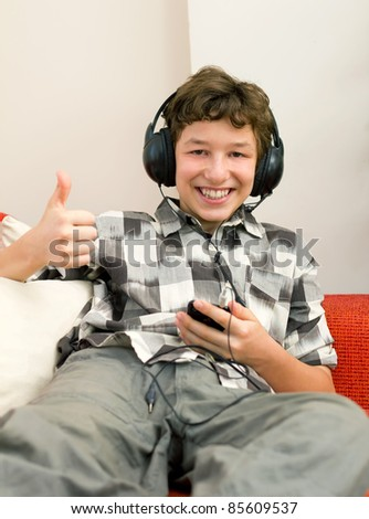 A preteen boy gives a thumbs up and a big smile to the great music he's listening to on his mp3 player through his big headphones as he sits back on an orange couch. - stock photo