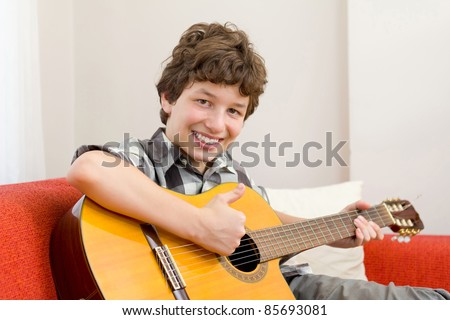 A preteen boy giving a thumbs up and a big happy smile as he holds his guitar and sits on an orange couch. - stock photo