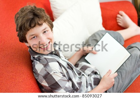 A preteen boy lounging on an orange couch with white pillows and reading a blank book looks up at the camera and smiles to show he enjoys reading. - stock photo