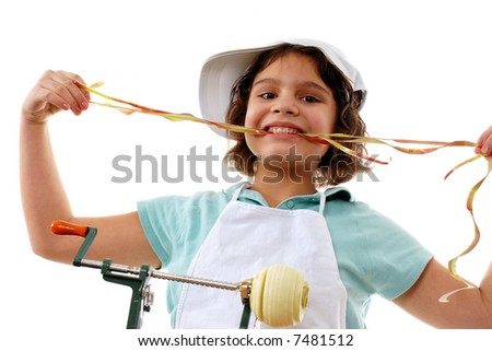 A preteen girl eating a long strand of peel she's removed from an apple on an apple-peeler.