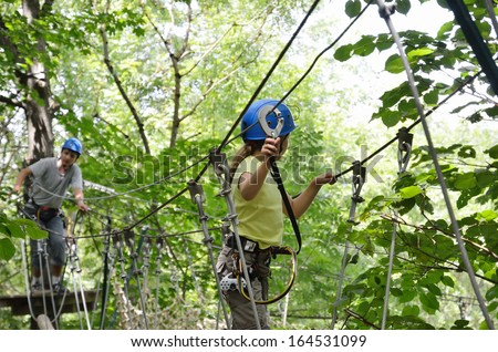A preteen girl is moving on the rope net. A teenage boy is resting on the platform. They are at the ropes obstacle course on trees high up. - stock photo