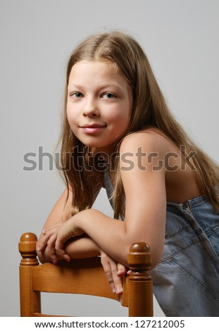 A preteen girl is smiling and looking at the camera. Her fair long hair are flowing. She is leaning on the back of chair. - stock photo