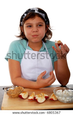 A preteen girl snitching the healthy fun food she'd just made. - stock photo