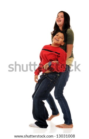 A preteen girl tickling her elementary brother.  Isolated on white. - stock photo