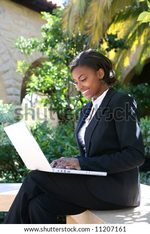 A pretty african american business woman at college on computer - stock photo