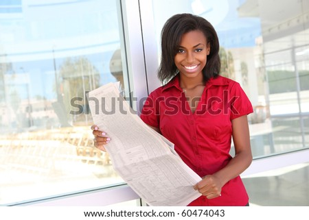 A pretty african american business woman at office reading newspaper