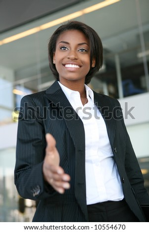 A pretty african american business woman offering a handshake - stock photo