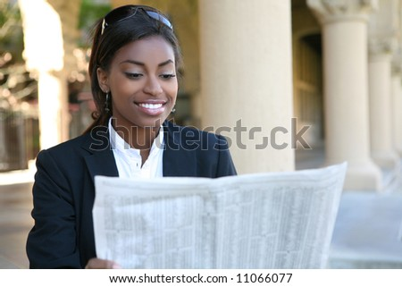 A pretty african american business woman reading newspaper - stock photo