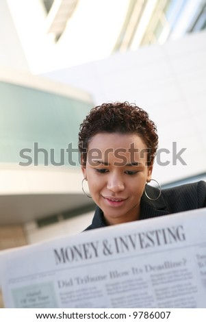 A pretty african american business woman reading the newspaper - stock photo