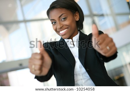 A pretty african american business woman with thumbs up - stock photo