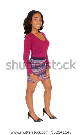 A pretty African American woman in a burgundy sweater and striped skirtstanding in profile, isolated for white background. - stock photo