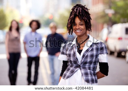 A pretty African American woman in the city with friends - stock photo