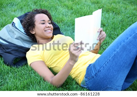 A pretty african american woman reading book in park - stock photo