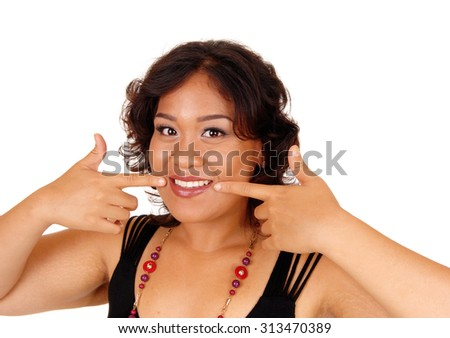 A pretty and smiling mixed raised woman pointing with her fingers