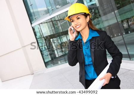 A pretty asian architect woman at building site on phone - stock photo