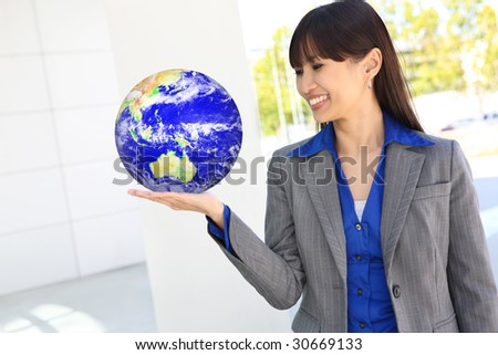 A pretty asian business woman at office holding globe of earth - stock photo
